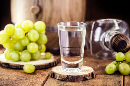 glass of distilled drink based on fermented grapes of high alcohol content, on rustic wooden background