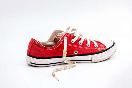 Side view of an old and dirty red sports shoe, made of elona, ​​used and dirty. Old shoe concept, young lifestyle