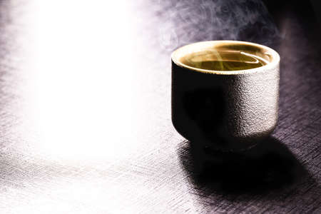 black oriental style cup, used for drinking sake or hot tea. Hot steam rising Stock Photo