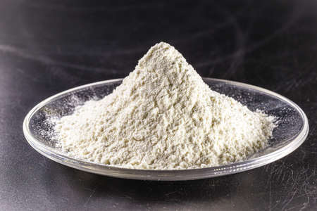 Pile of calcium sulfate on white background, known as micronized alabaster or micronized plaster