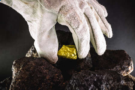 miner hand removing gold stone from excavation mine
