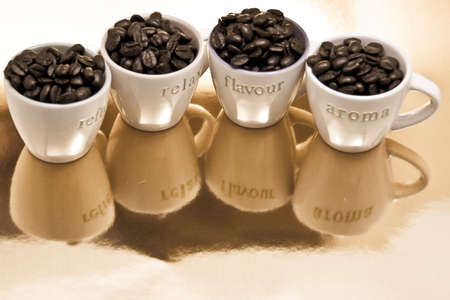 Four coffee cups with fresh roasted beans photo