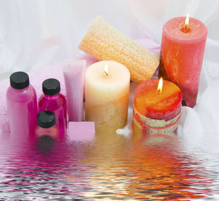 Spa items with lit candles on rippled water Stock Photo