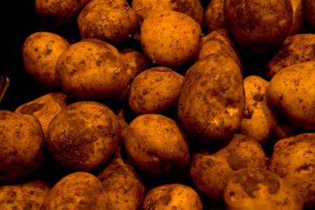 Fresh unwashed potatoes at fresh food market
