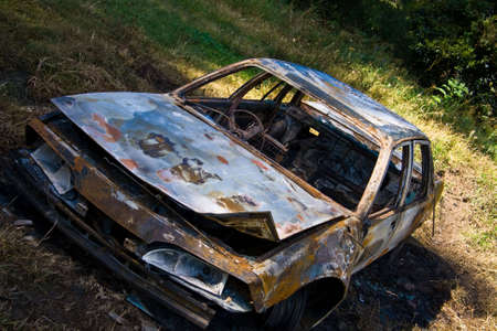 Burned out car abandoned in paddock Stock Photo
