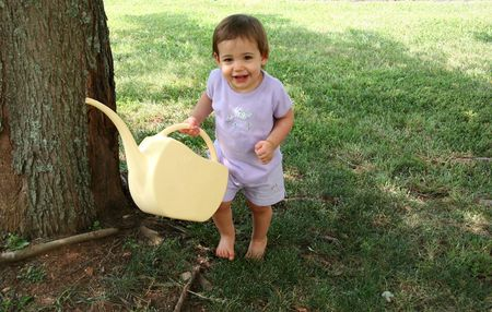 Adorable  girl holding a watering can.