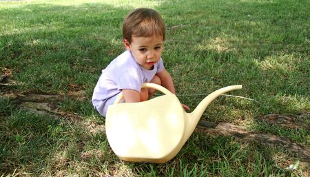 Picture of a  girl with her hand in a watering can.