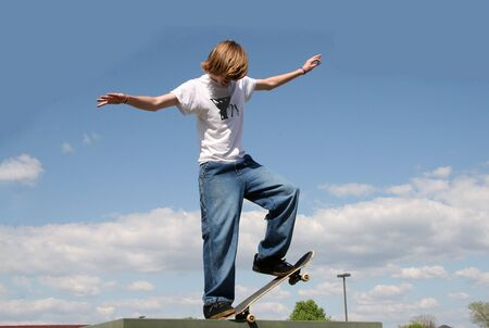 Skateboarder balancing on edge high in clouds.