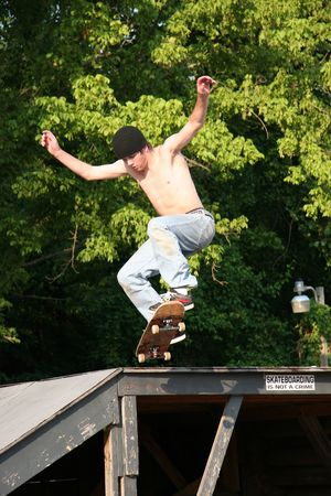 Male teen skateboarder jumping off a platform at a skatepark. Stock Photo