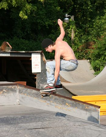 Male teen skateboarder grabbing his board while in the air.