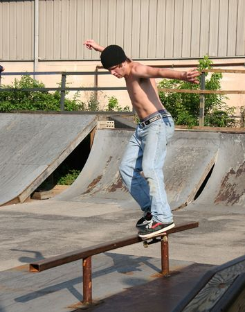 Male teen skateboarder sliding on rail at skate park. Stock Photo