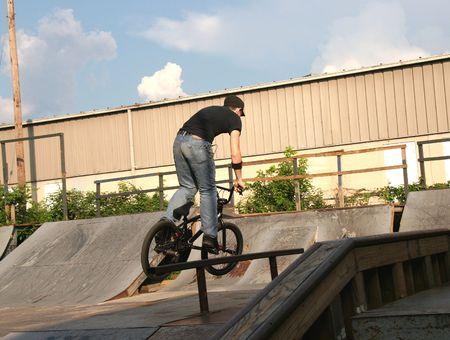 15 18: BMX biker doing tricks at skate park.