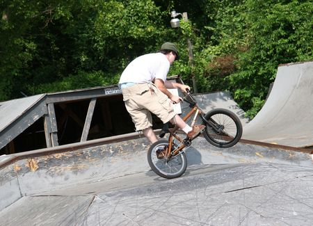 BMX biker doing tricks at skate park.