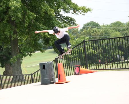 Teen male skateboarder jumping a cone at a skatepark.