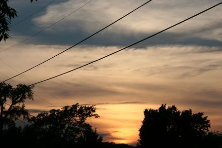 Sunset on stormy night. Wind blowing trees under powerlines and cloudy, dark sky.