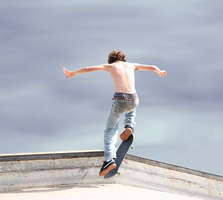 Teen skateboarder and board high in the air with shadow on ground. Stock Photo