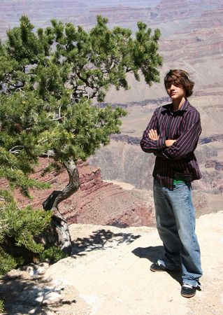 Teen boy sightseer standing near edge of Grand Cayon.