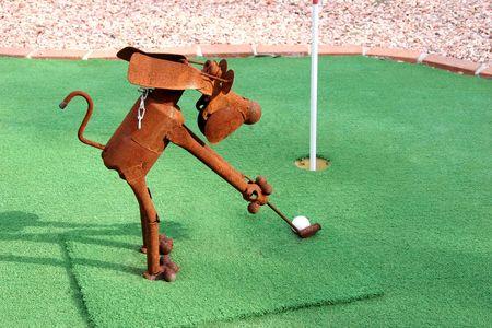 Rusty tin dog playing golf.