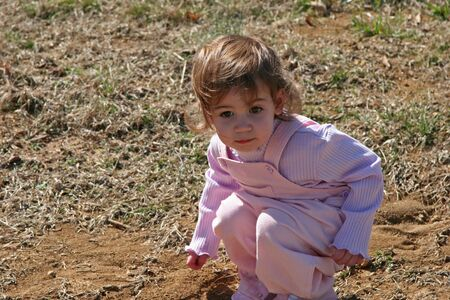 Beautiful  girl playing in dirt and looking serious.
