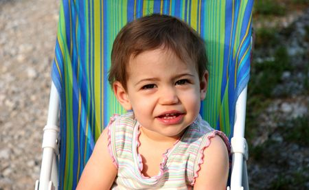 Beautiful  girl in push chair squinting.