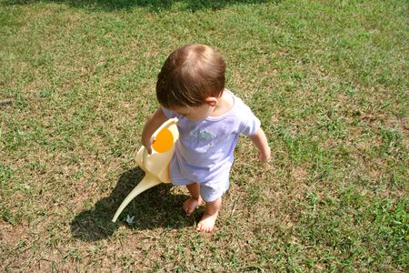 Adorable  girl watering lawn.