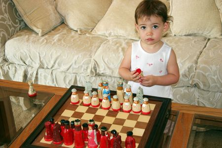 Close-up of a beautiful one-year-old  girl playing with chess pieces. Stock Photo
