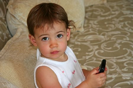 Close-up of a beautiful one-year-old  girl with a TV remote. Stock Photo