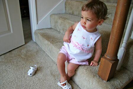 sandels: Beautiful  girl putting shoe on wrong foot. Stock Photo