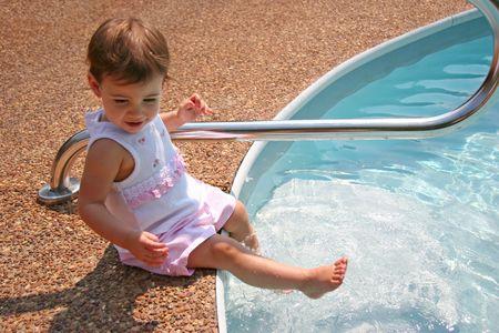 Beautiful  girl splashing water in pool with feet. Stock Photo
