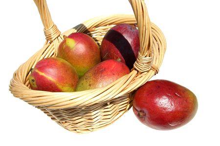 Close-up of basket of mangos over white.