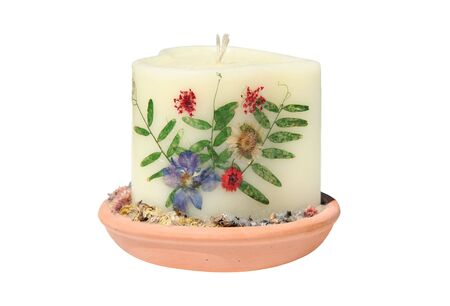 Close-up of off white candle beautifully decorated with flowers. Stock Photo