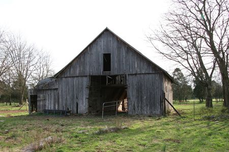 Abandoned gray wooden barn with grass in front and trees behind shot at sunset.