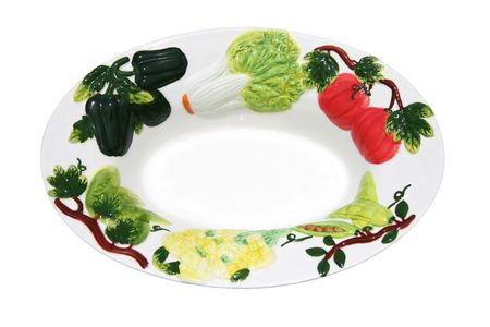 Close-up of white ceramic bowl decorated with a ring of vegetables.