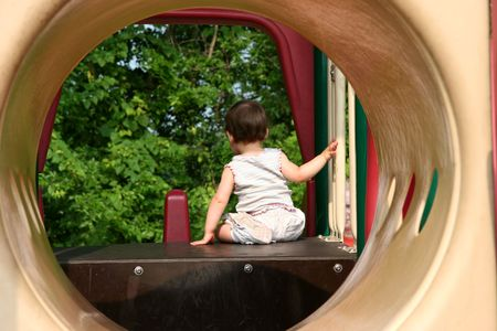perching:  girl getting ready to go down a slide with foot turned back.