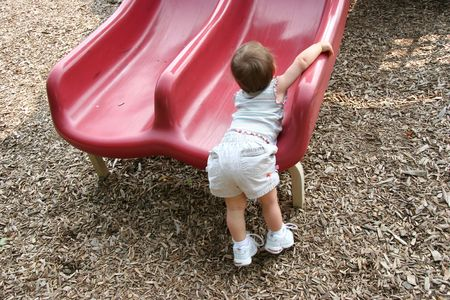 girl trying to climb on red slide at playground.