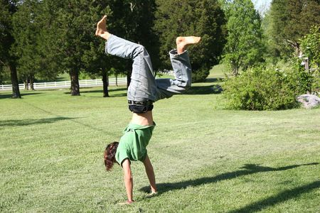 Teen boy doing hand stand on pretty lawn.
