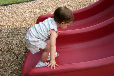 Baby girl walking up red slide at playground. Stock Photo