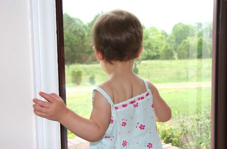 Tiny  girl looking out of window.