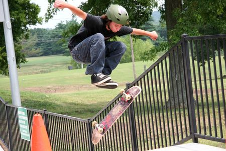 12 13: Skateboarder jumping cone and flipping his board. Stock Photo