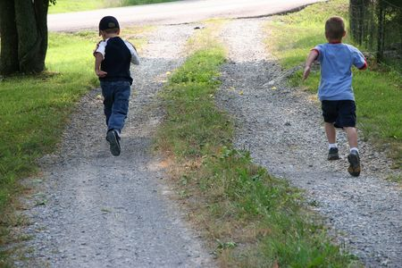 Five year old boys racing to the end of drive. Stock Photo