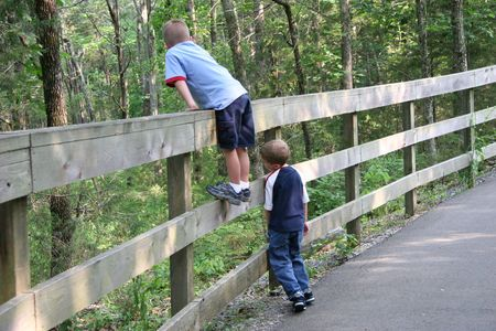One boy climbing fence. tired boy leaning against fence.