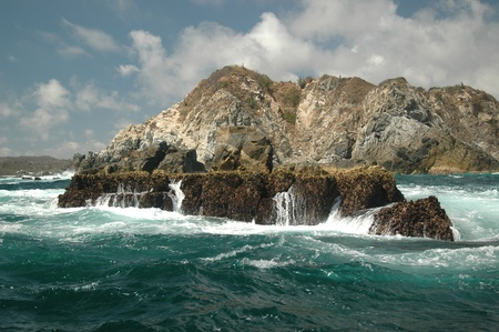 Rough surf near Huatulco, Mexico. Waves pounding on the rocky shore and islands near the coastline.
