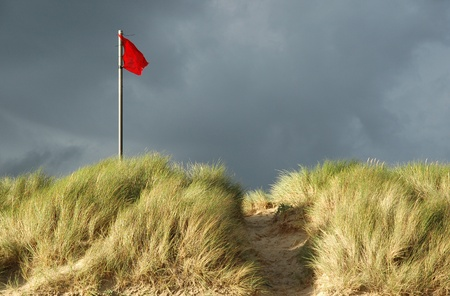 Red danger flag on a beach. Warning flag at the top of a grass-covered sand dune indicating unsafe swimming conditions.