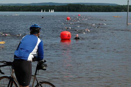 Cyclist watches the swimmers in the triathlon. Ottawa Riverkeeper Triathlon 2009. Editorial