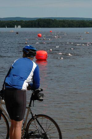 britannia: Cyclist watches the swimmers in the triathlon. Ottawa Riverkeeper Triathlon 2009. Editorial