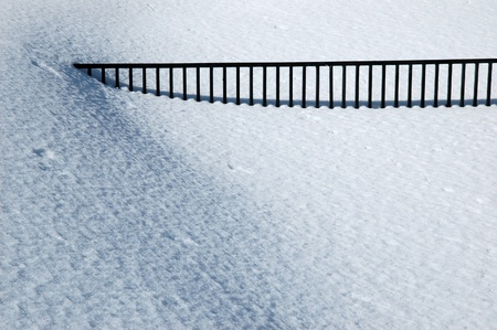 Black fence in white snow.