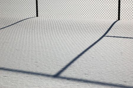 Minimalism type shot of a wire fence and a long shadow cast across the white snow.