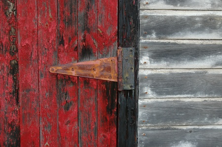 Door hinge and flaking red paint on a shed door. photo