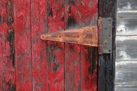gritty: Door hinge and flaking red paint on a shed door. Stock Photo