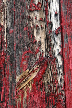 flaking: Black stains on shed siding board with flaking red paint.